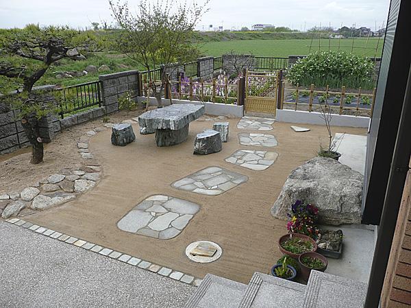 石のテーブルとイスが素敵なお庭